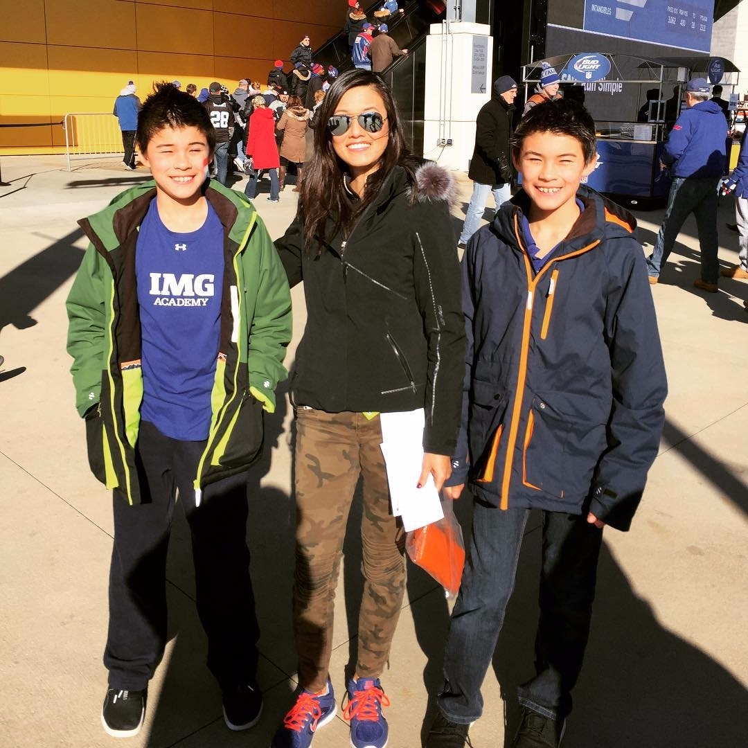 Betty Liu standing with her twin sons.