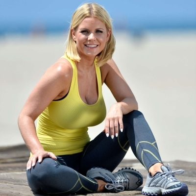 The body-hugging outfits have perfectly accentuated Carrie Keagan's body measurements. She wearing a yellow tank top along with yoga pants and sports shoes.