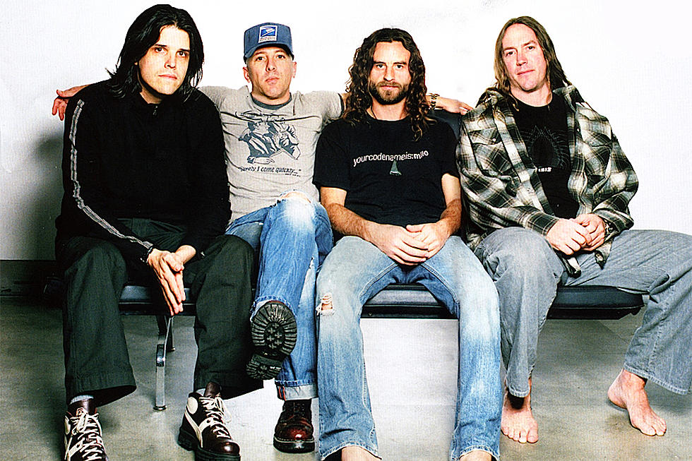 The Tool band members sitting on a long chair