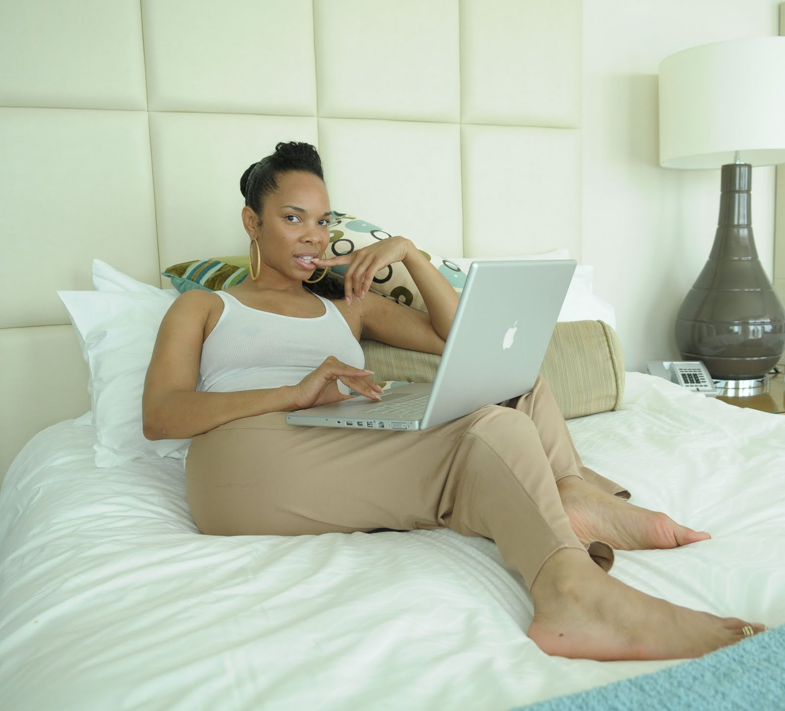 Cherie Johnson lying on a bed. She has a laptop on he lap.