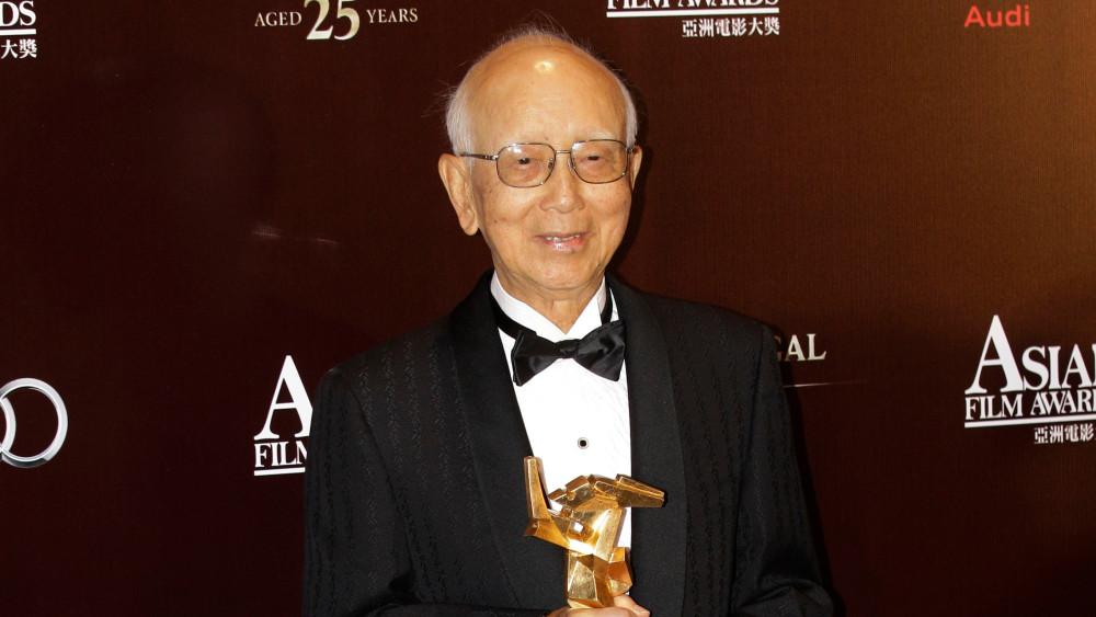 Raymond Chow holding a award