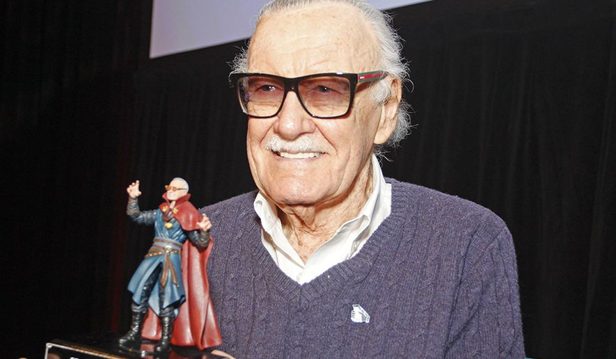 Stan Lee with a action figure of Doctor Strange
