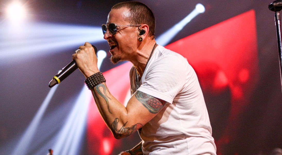 Chester Bennington screaming into mic, he's wearing sunglasses