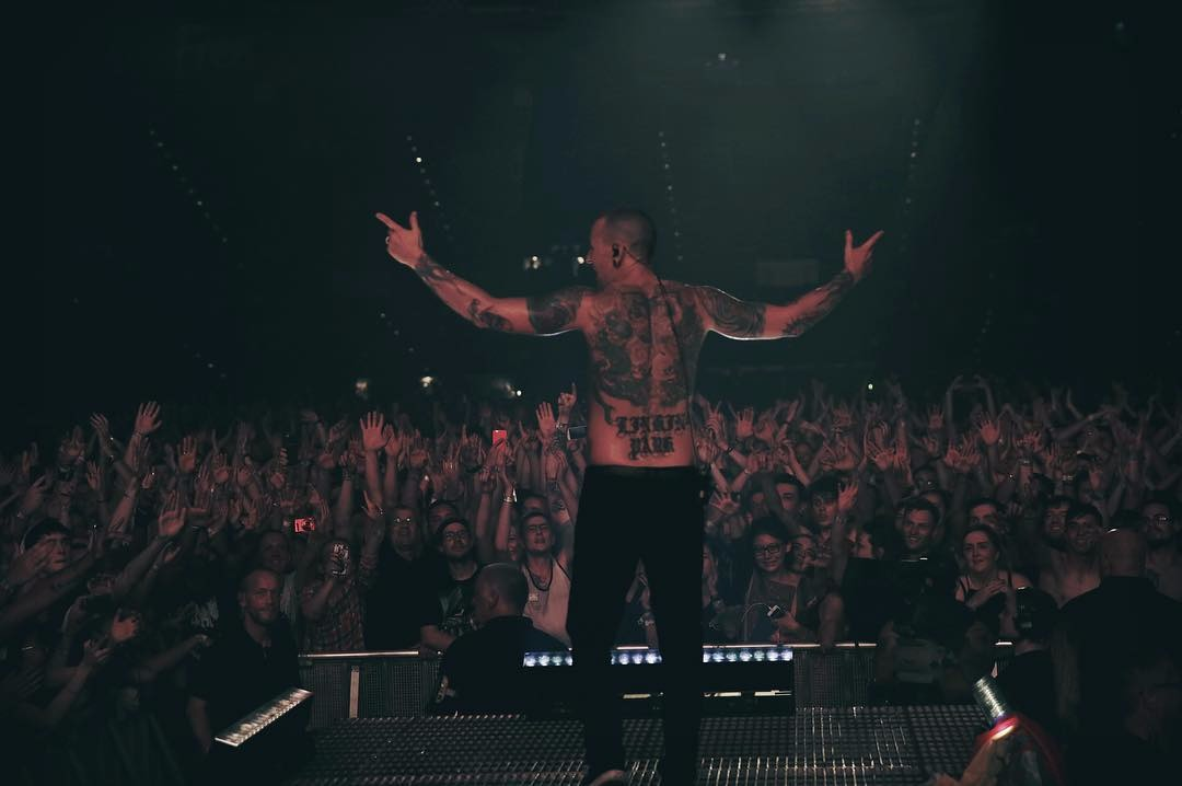 Chester Bennington shirtless on stage, he's facing the crowd in front of him so that his back is faced to the viewer