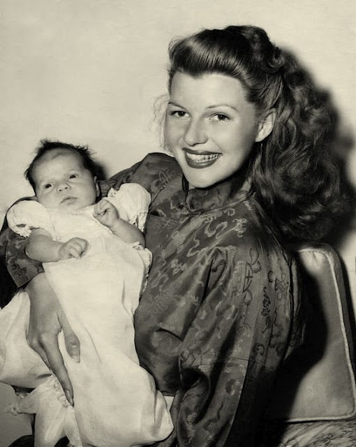 Rita Hayworth is giving a big smile, holding her daughter in her hands.