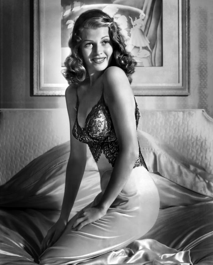 Rita Hayworth is sitting on a bed, showing her side profile.