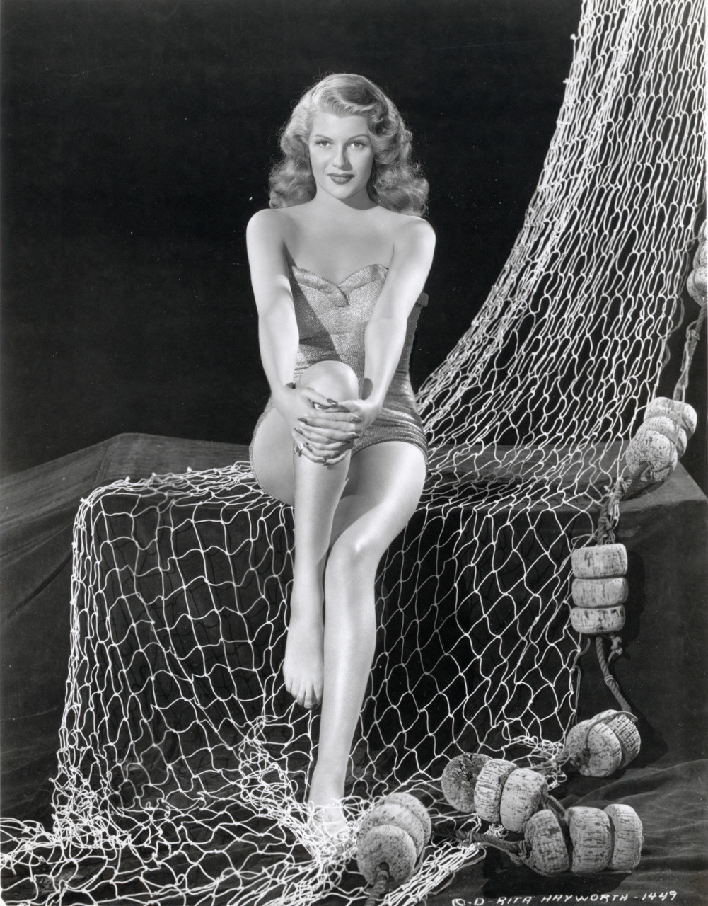 Rita Hayworth is sitting, holding her knee with both her hands. She is sitting on the net and is wearing a swimsuit.
