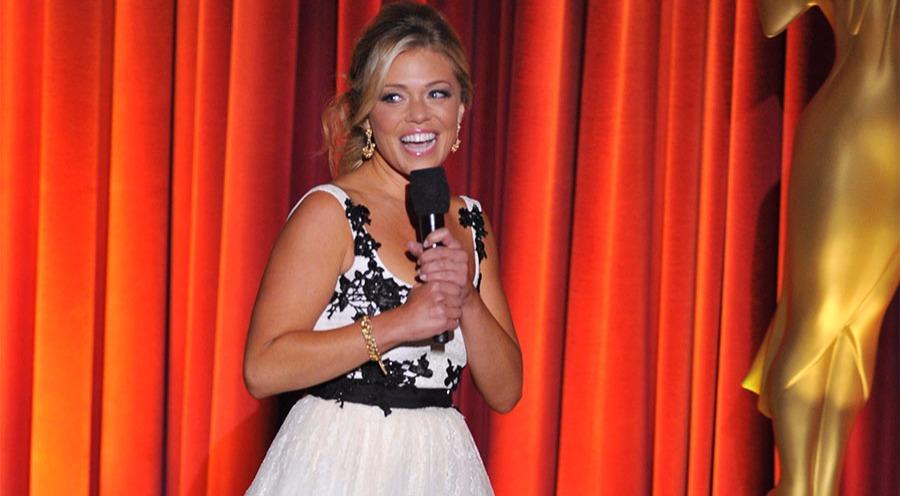Lauren Sivan smiles with a mic in hand