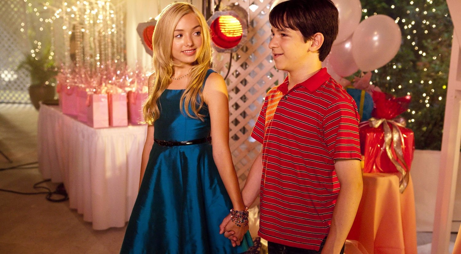 Peyton List and Zachary Gordon clasping hands on set of movie 'Diary of a Wimpy Kid: Dog Days'. They play Holly Hills and Greg Heffley in the film fraanchise.