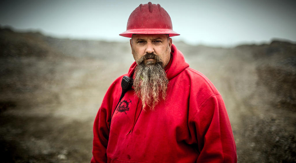 Todd Hoffman is posing for the camera on the mining area. He facing straight at the camera. He is wearing a red hoodie and a red helmet.
