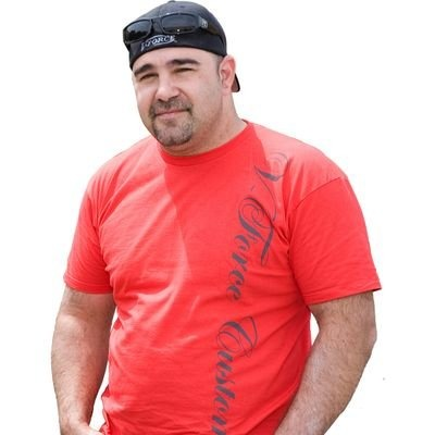 "Vincent ""Vinnie"" DiMartino standing for camera with hands in pocket. He has a red tshirt with baseball cap pulled to the back with sunglasses perched on it, his signature style."