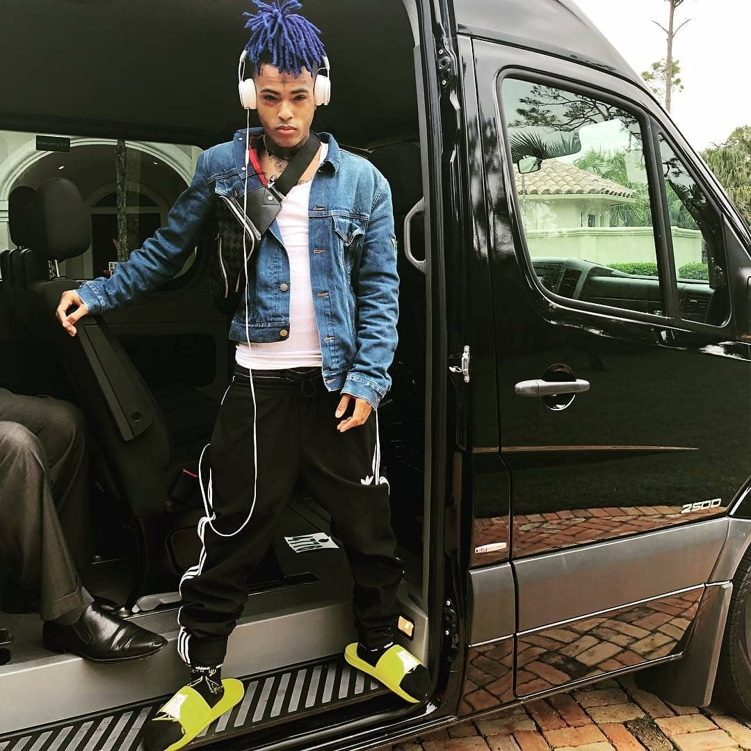 XXXTentacion is standing on his car wearing a jeans jacket