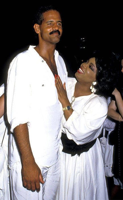 Oprah Winfrey and Steman Graham posing for a picture. The Couple is matching white dress. Oprah Winfrey and Stedman Graham got engaged in 1992.