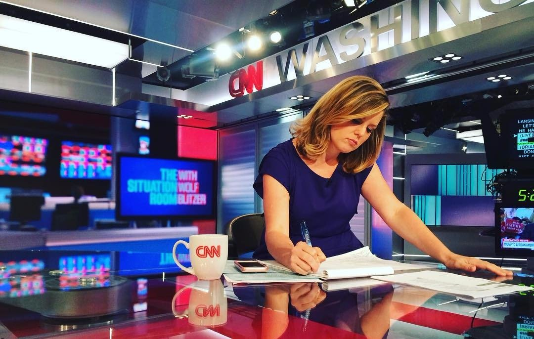 Brianna Keilar writing at a desk, there's a CNN mug on the table