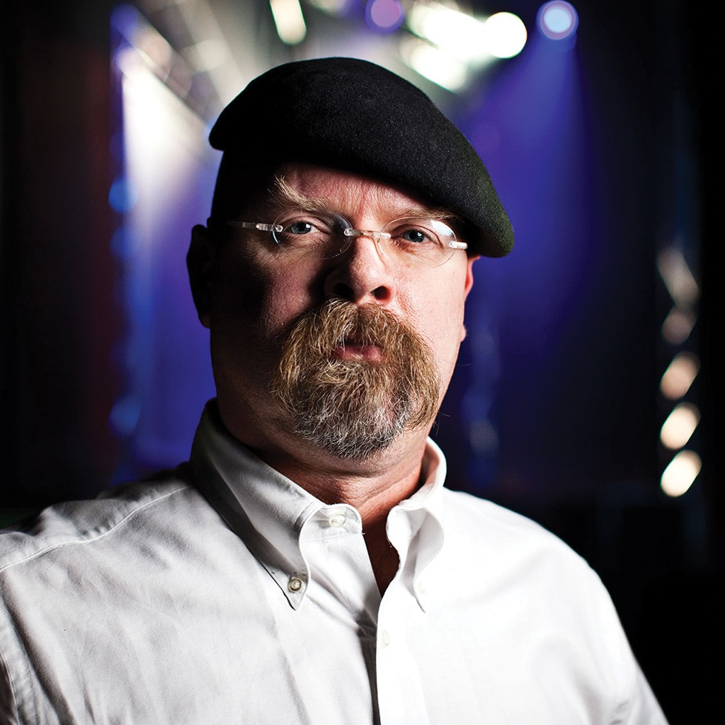 James Hyneman is looking at the camera wearing a nerd glass and black cap. He is well-known as co-host of TV show, MythBusters.