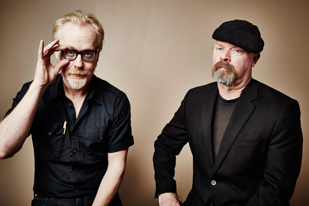Jamie Hyneman is posing for the camera with his MythBusters co-host, Adam Savage. Jamie is looking away from the camera while Adam is holding his glass with his right hand.
