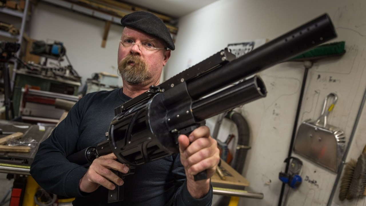 An American special effect expert, James Hyneman is holding a gun on his hand. He is wearing dark beret, no-rim glasses and black t-shirt.