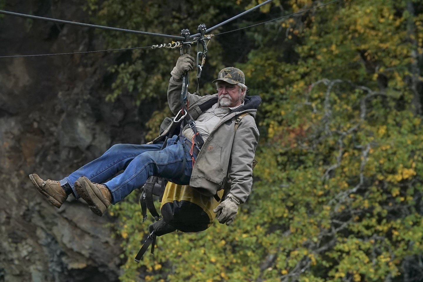 Dakota Fred pulls the stunt of sliding on a rope. His right is holing the harness while his body is leaned back. He is carrying a huge yellow bag on the side. He is wearing a camo cap, light brown jacket, jeans and a hiking boot.