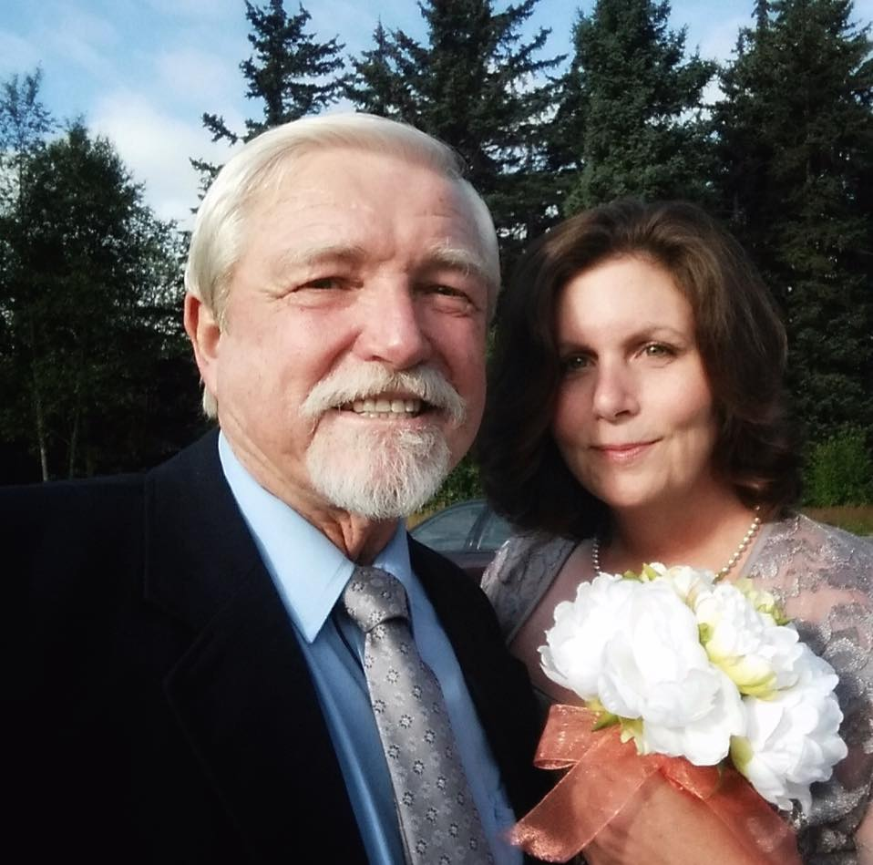 Dakota Fred is standing alongside of his wife, Jennifer Sheets. The couple is slightly smiling at the camera. Dakota is wearing a blue shirt and a black coat. Jennifer is holding a flower on her left hand.