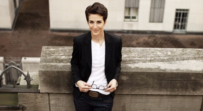 Rachel Maddow leaning against a wall, holding glasses in hand