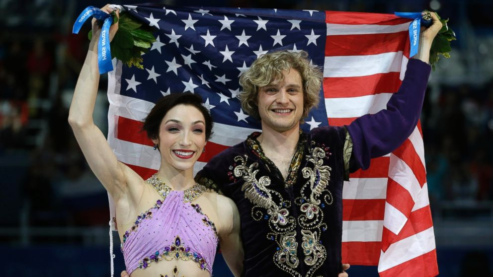 Meryl Davis and Charlie White holds American flag after the win in the 2014 winter Olympics at Sochi.