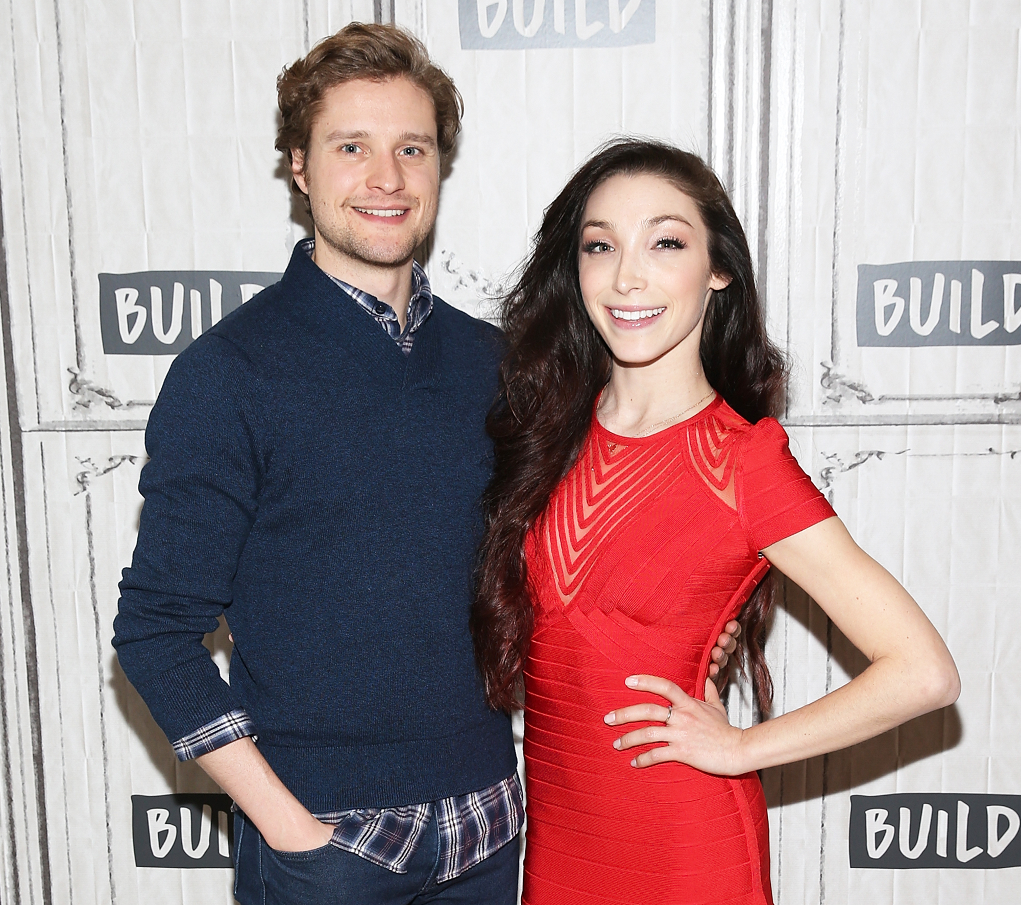 Meryl Davis and Charlie White are posing with a smile. Meryl looks great in red dress and Charlie looks total clad in blue sweater and patterned shirt.
