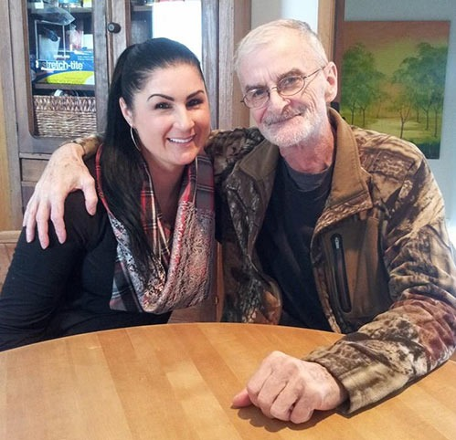 Randy Weaver is sitting along side his daughter, Sara Weaver. Both Randy and Sara is smiling faintly as they look at the camera. Randy has got his arms around Sara's shoulder.