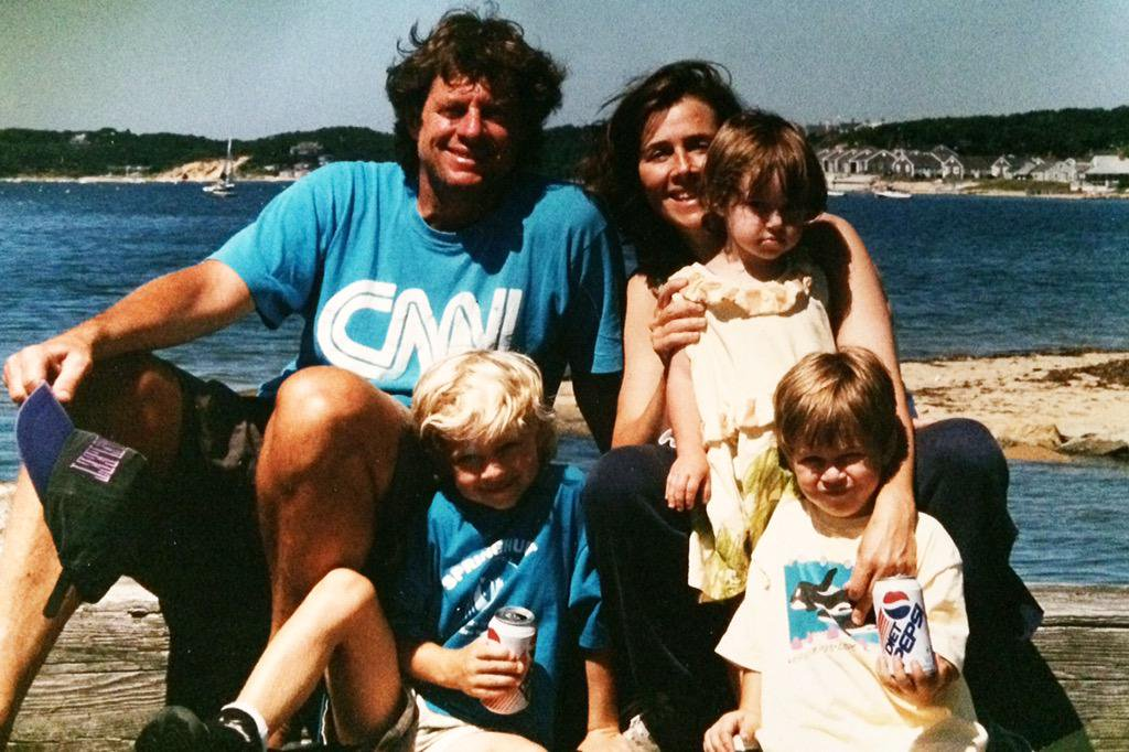 A young Meredith Vieira holding her daughter, her husband Richard is sitting beside her, her sons are sitting a step lower, there's a sea behind her