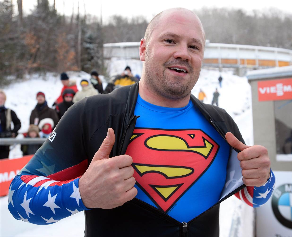 Steve Holcomb showing off the superman logo printed on his t-shirt