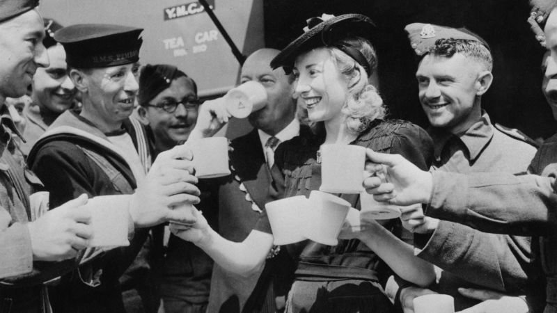 Awestruck soldiers raise their mugs to toast singer Vera Lynn during an appearance