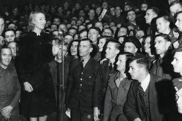 Vera sings to a crowd of soldiers. The black and white photo was taken sometime around the second world war.