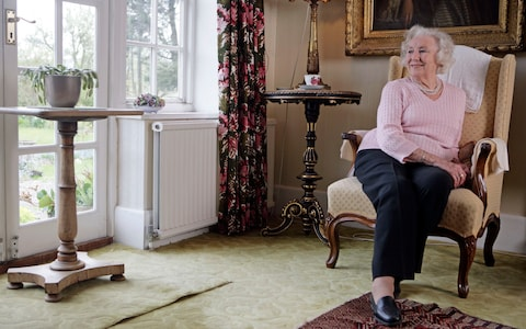 Vera relaxes in a sofa at her Sussex home