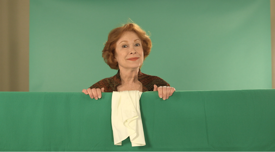 Linda Kaye Henning reviving the scene of Petticoat Junction. She is standing behind green curtain.