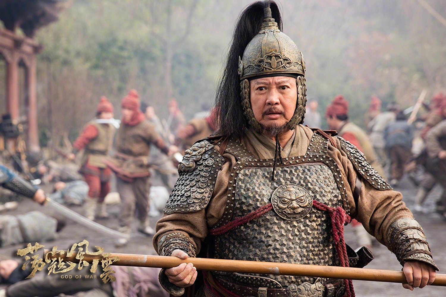 Sammo Hung looks fierce in custom for the movie God of Wars. He is holding a Javelin throw in his hand.