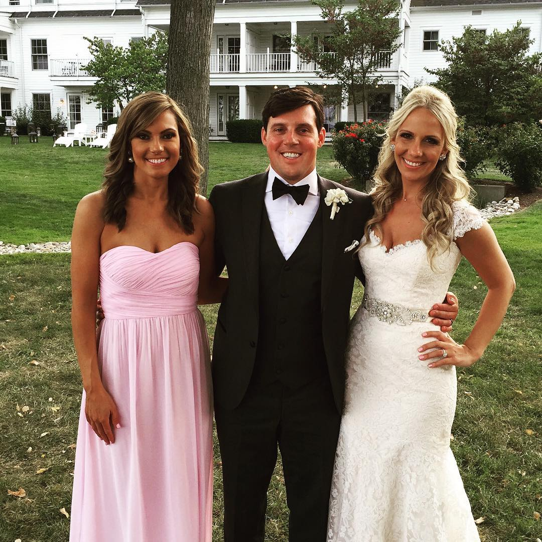 Lisa Boothe posing for a picture with her brother and sister in law she is wearing a white dress