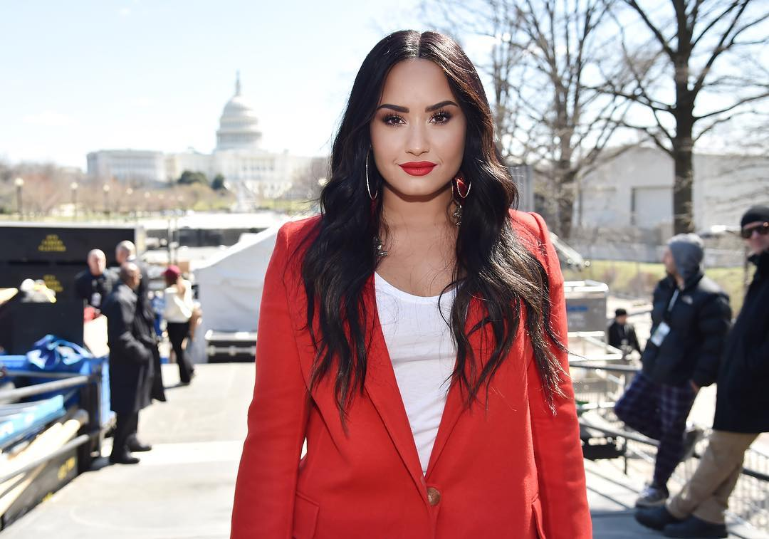 Demi Lovato is wearing red coat and white t-shirt