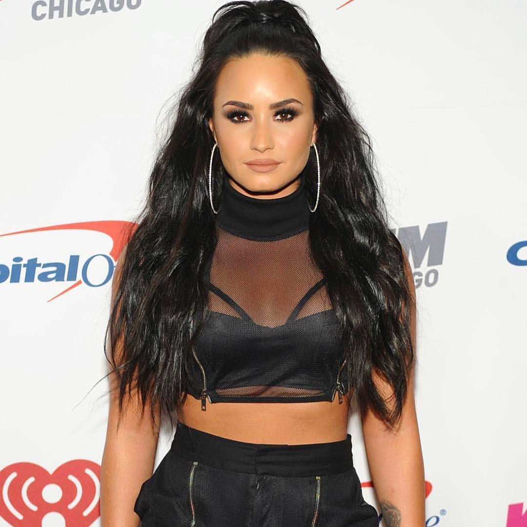 Demi Lovato is wearing a black outfit. She looks stunning in the smoky eyes makeup.