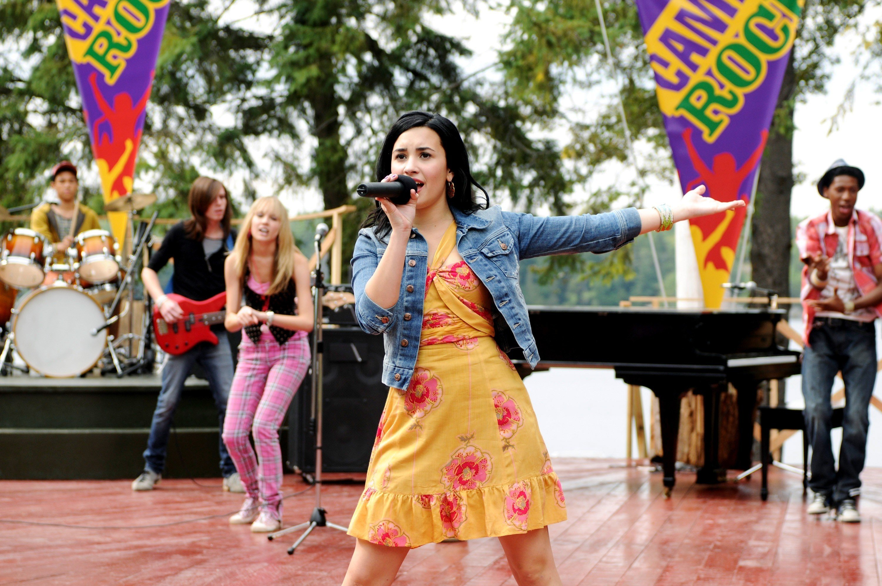Demi Lovato holding a  mic and performing on stage with a her Camp Rock team
