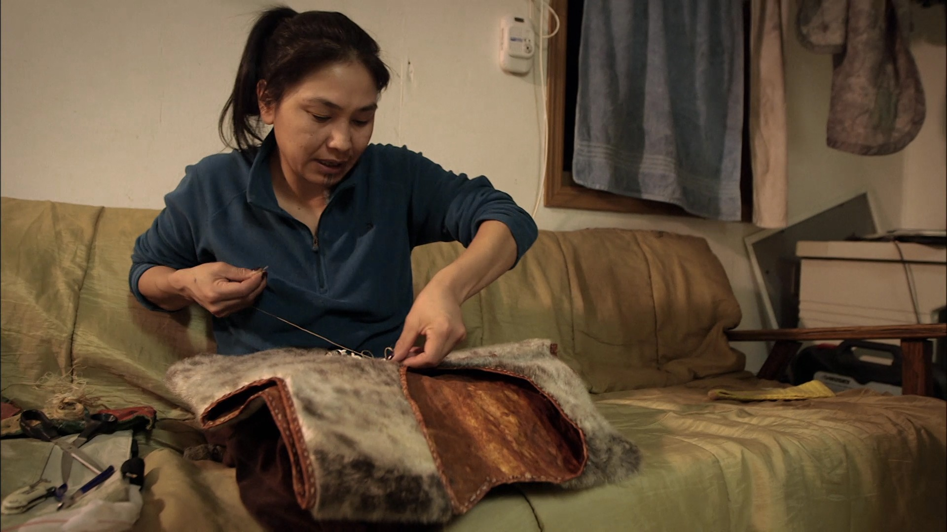 Agnes Hailstone is stitching a coat out of a animal fur. She is sitting in a sofa in her living room.