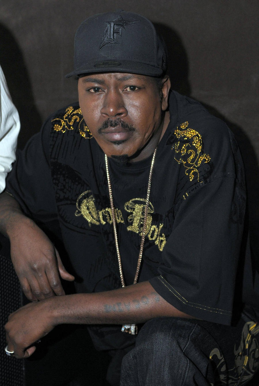 Trick Daddy is wearing all black from his cap to t-shirt to pant.