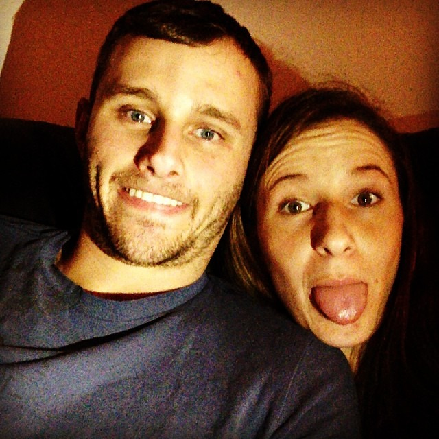 SSundee and his wife Maddie are making weird faces. SSundee is showing his teeth and Maddie has her tongue out.