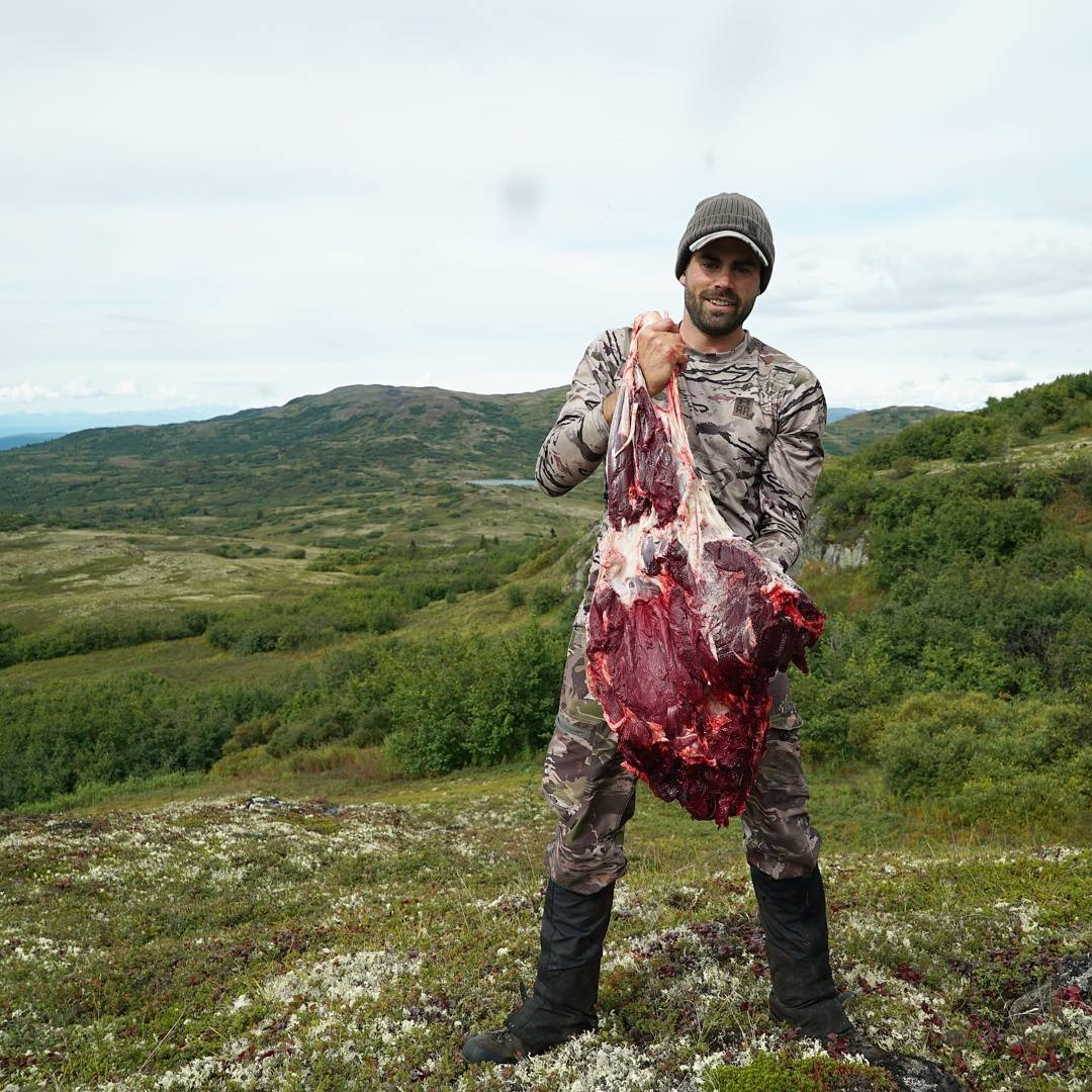 Remi Warren carrying a lump of raw meat from his hunt. He is standing in middle of a greenery scenario.