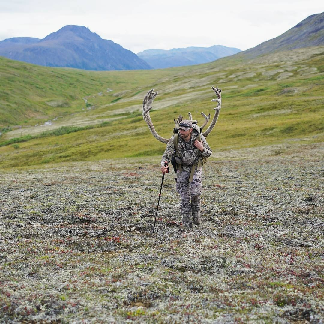 Remi Warren climbing up a hill, he is carrying his hunt on his back. He is using a walking stick.