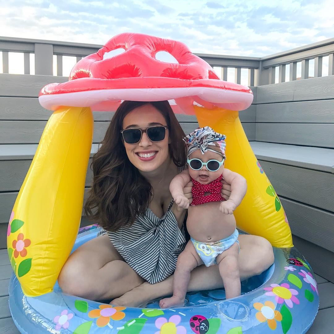Marina Squerciati is holding her baby daughter sitting in a mini pool. Both Marina Squerciati and her daughter look adorable wearing sunglasses.