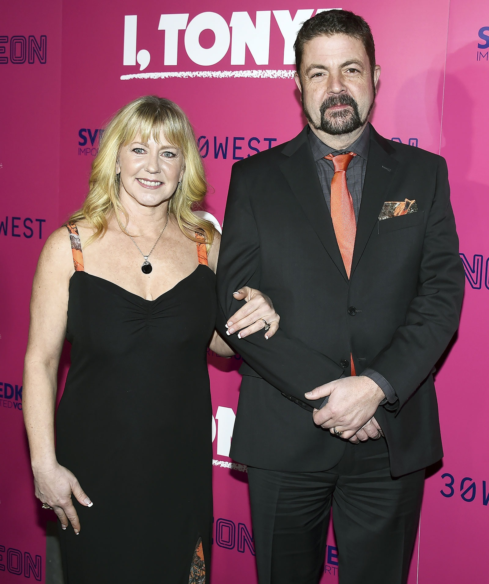 Joseph Jens Price and his wife, Tonya Harding makes a beautiful couple. They are wearing a matching attire. Joseph is wearing a black suit and orange tie while Tonya has put on a black dress with orange stripes.