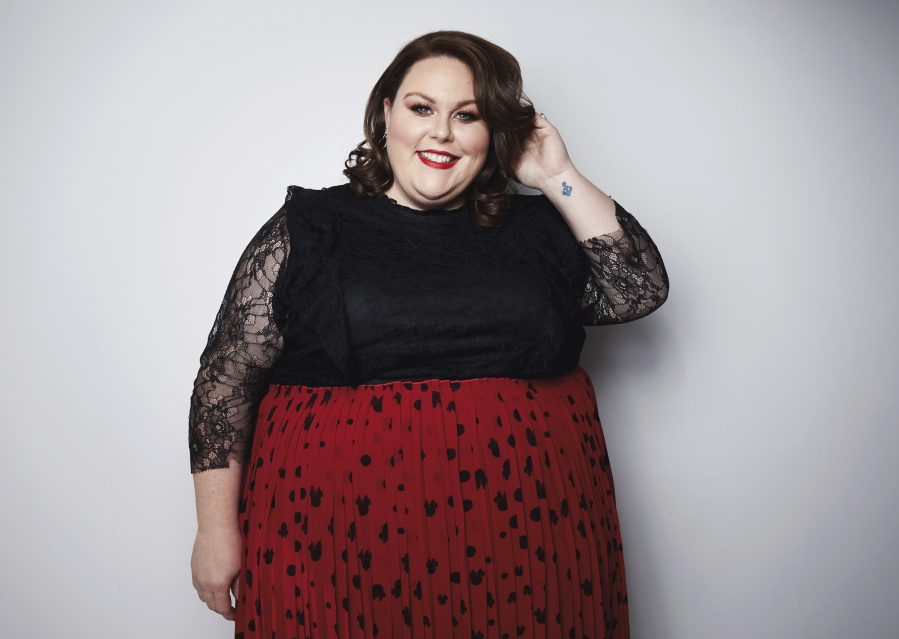 Chrissy Metz smiling, wearing a black and red dress
