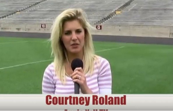 Courtney Roland standing on the football ground. She is holding a mic in her right hand.