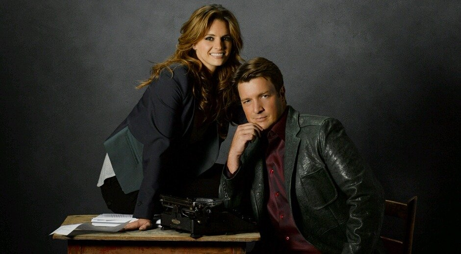 A still from Castle. Nathan Fillion is portraying Richard Castle and Stana Katic is portraying Katherine Beckett. Stana is sitting on a table while Nathan is sitting on a chair, resting his chin on his hand.