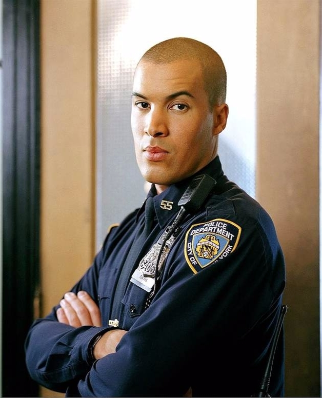 Coby Bell as officer Ty Davis, Jr. in the drama series Third Watch. He is giving a serious look with one of his eyebrows up. Coby Bell is with his hairs in the photo.