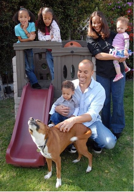 Coby Bell and his family are off spending quality times. His elder daughters are standing in a slide, Coby and his wife are holding their new born.